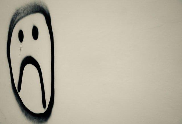 Trauriges Gesicht an Wand, weil Prokrastination entstanden ist