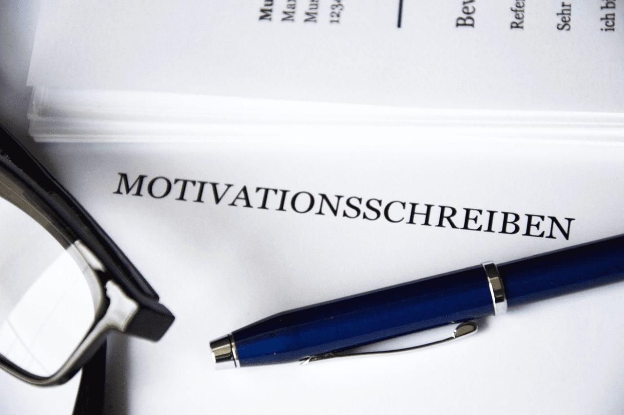 Auf dem Bild sieht man eine Brille und einen Kugelschreiber über einem Blatt auf dem Motivtationsschreiben fürs Studium steht
