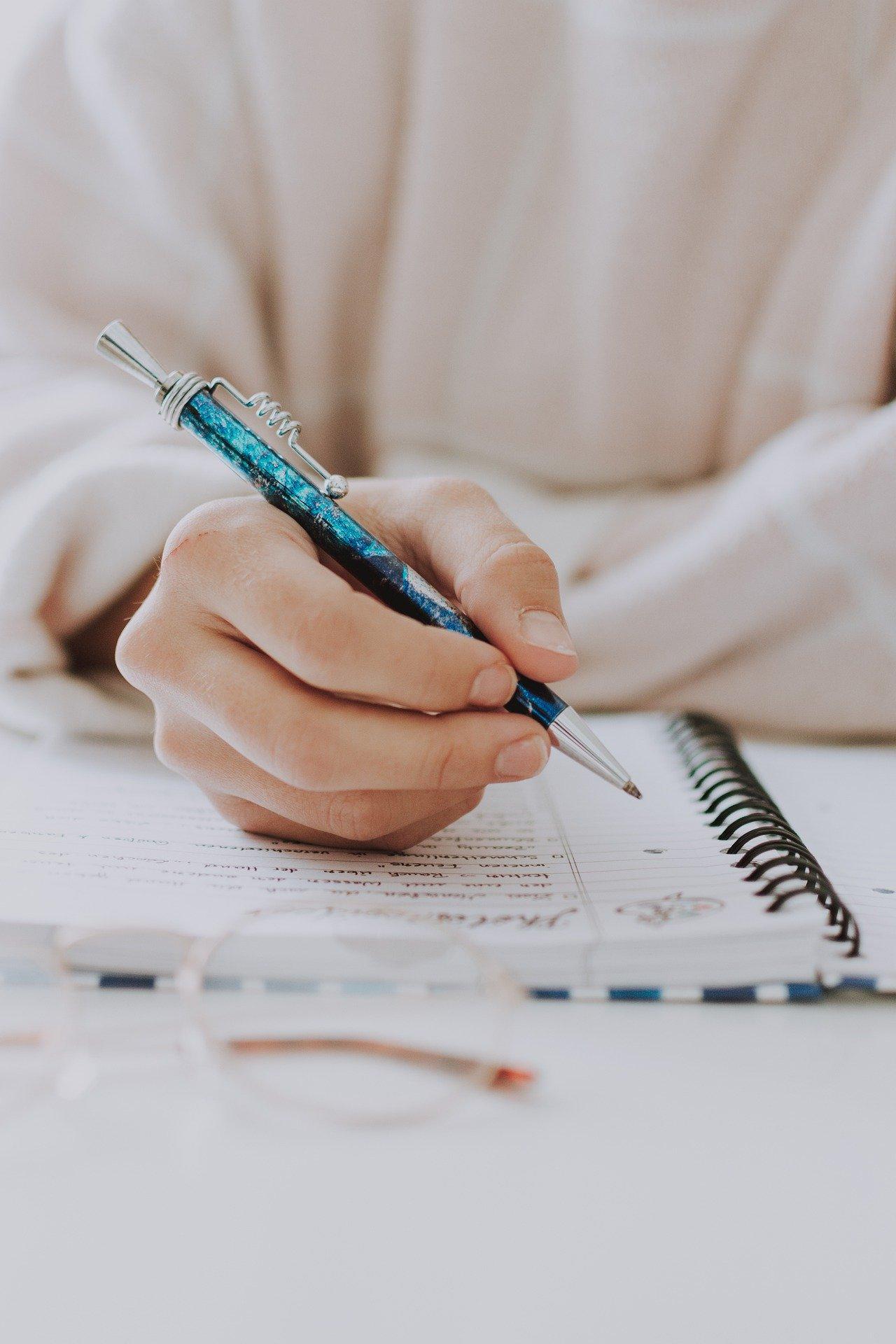 Eine Schülerin macht Notizen für ihr Motivationsschreiben fürs Studium.